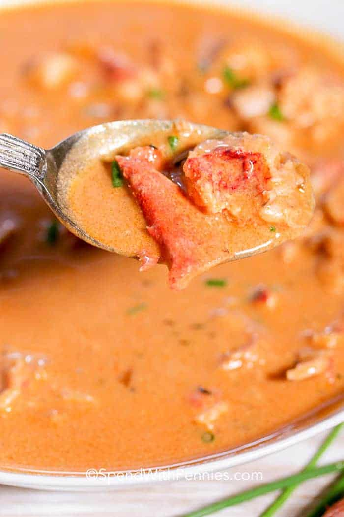A spoonful of lobster bisque with chunks of lobster claw