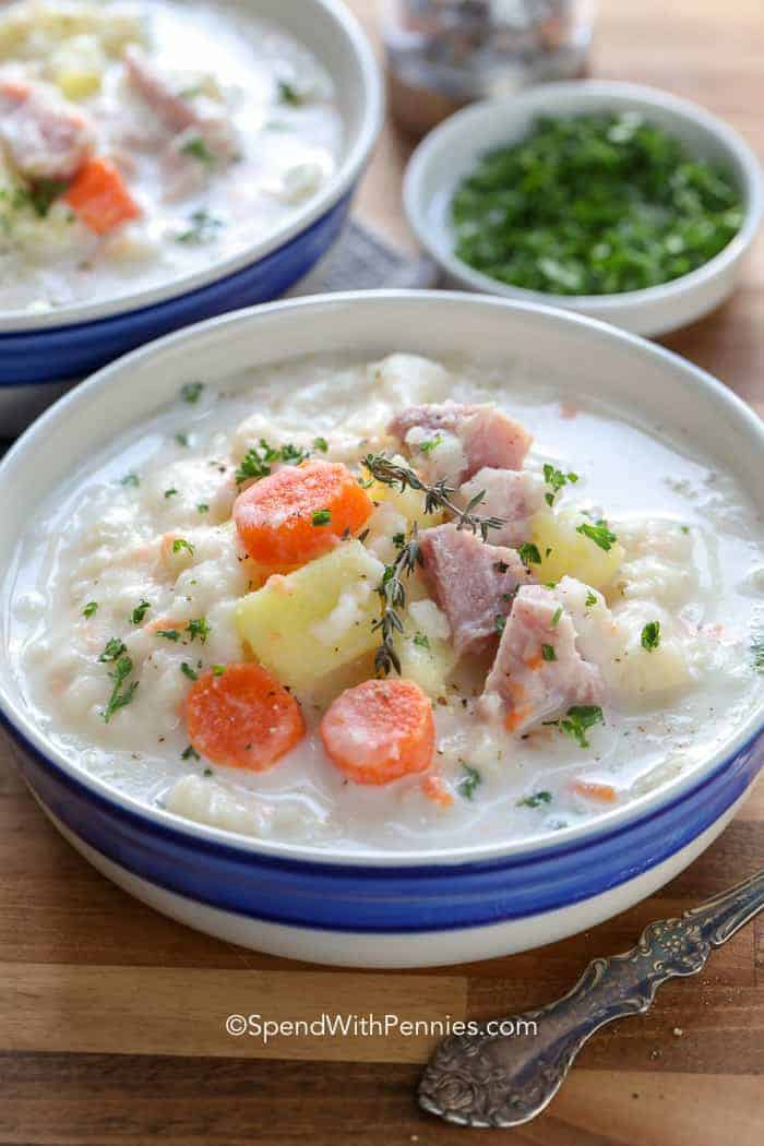 Crockpot ham and potato soup in a big bowl topped with fresh herbs.