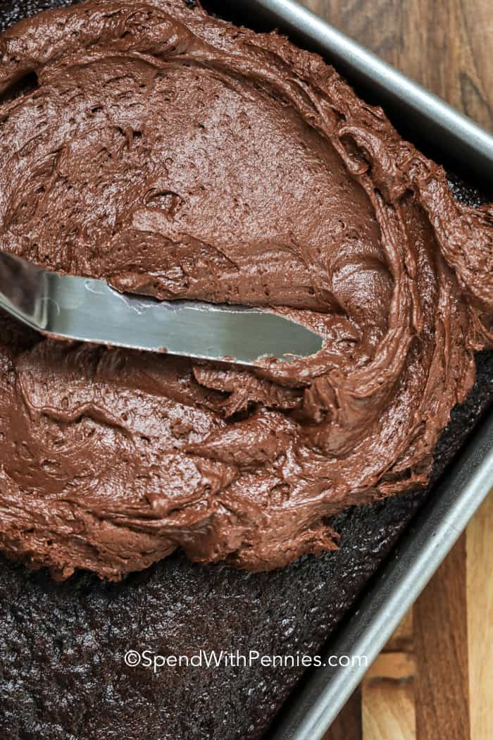 Spreading chocolate buttercream frosting over a chocolate cake