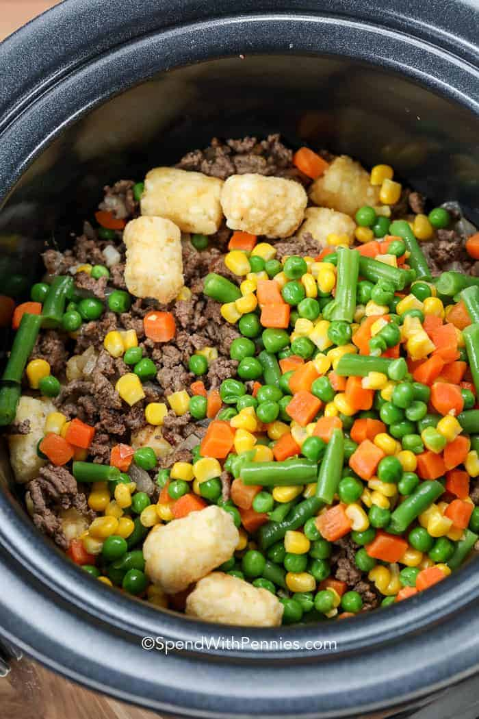 A slow cooker filled with cooked ground beef, vegetables and tater tots