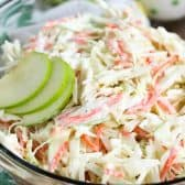 Clear bowl of Creamy Apple Slaw with slices of apples