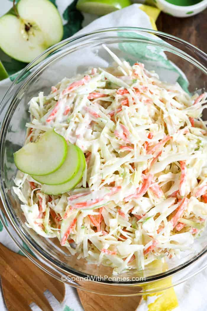 A bowl of creamy apple slaw and fresh granny smith apples.
