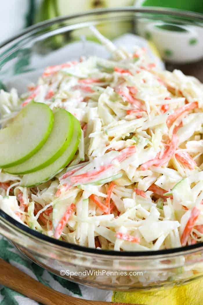 A large bowl of creamy apple slaw with apple slices on top