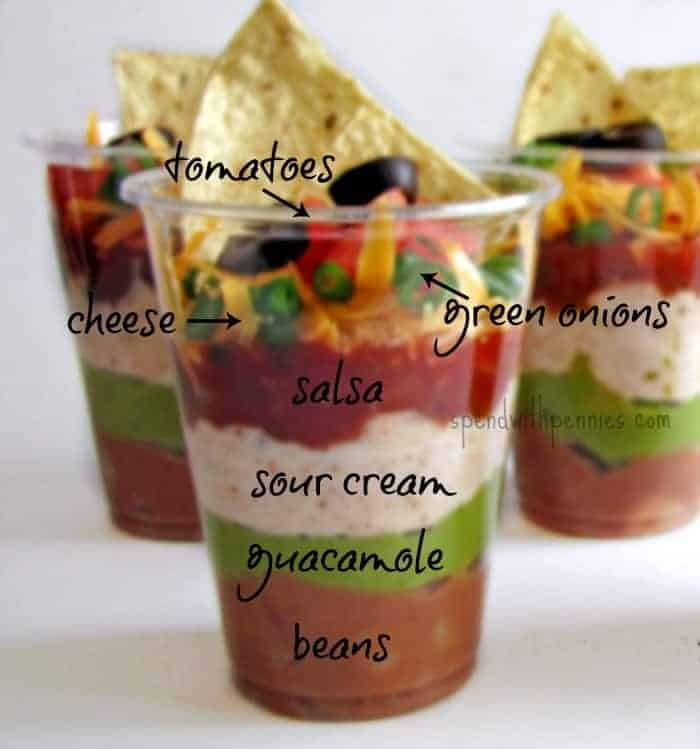 individual seven layer dip ingredients in cups with a tortilla chip