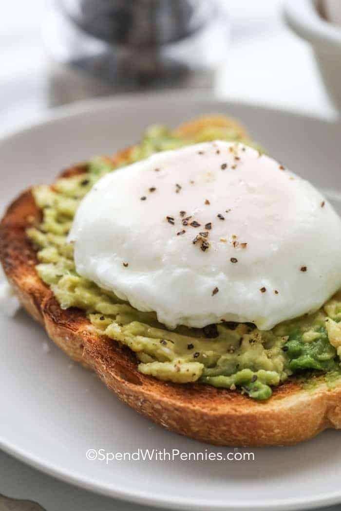 A perfectly poached egg on a piece of avocado toast topped with black pepper.