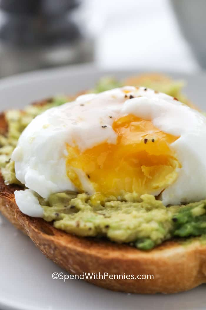 A poached egg with the yolk broken on a piece of avocado toast.