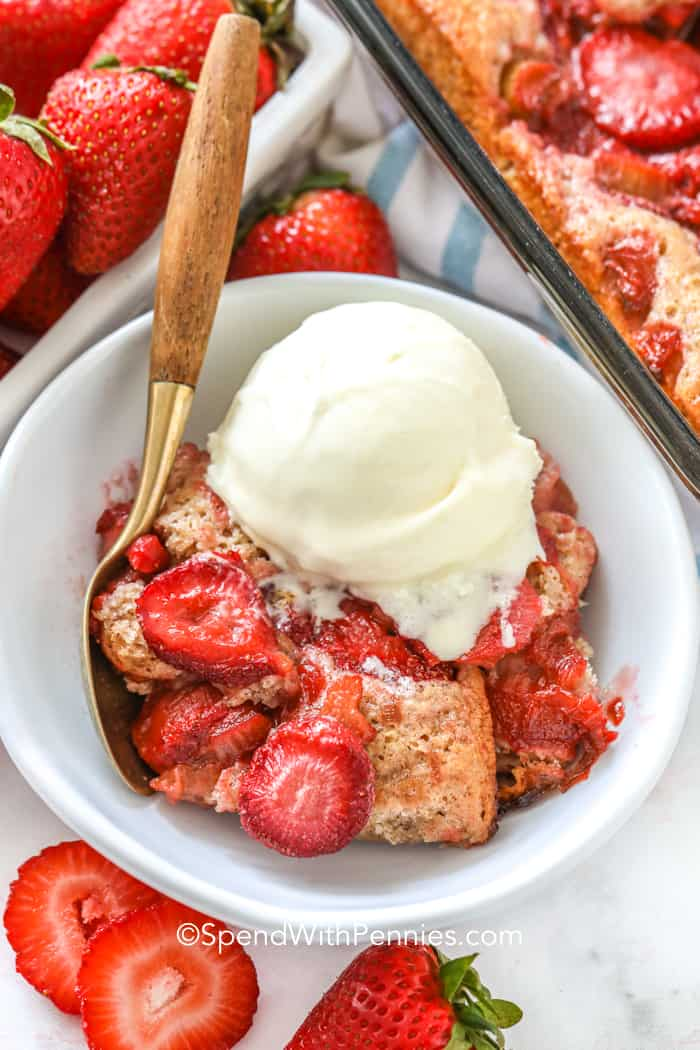 Strawberry Rhubarb Cobbler in a white bowl with vanilla ice cream and a spoon