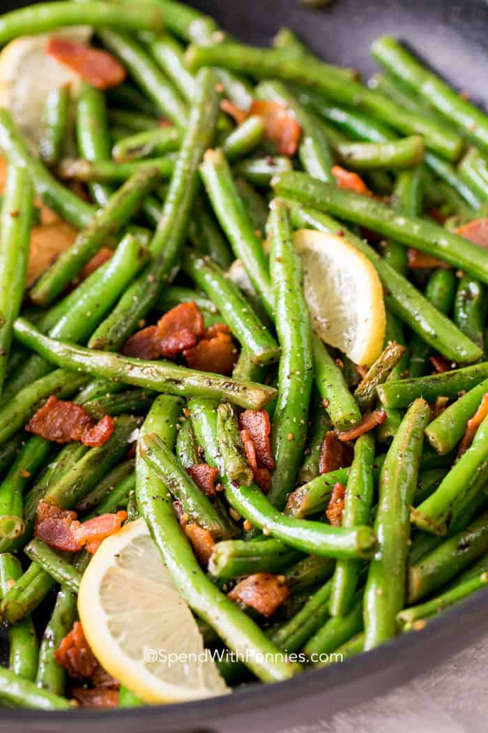 Green Beans with bacon is one of our all time favorite side dishes! Fresh green beans are sauteed with bacon and garlic until tender crisp.  A squeeze of fresh lemon is added just before serving making these the perfect easy side!