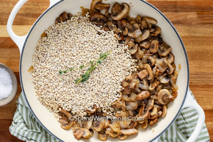Mushroom barley risotto ingredients in a pot.