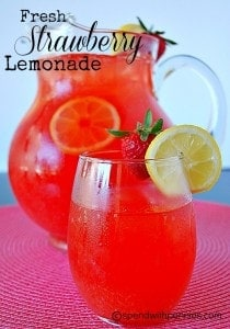 fresh strawberry lemonade in a glass with a pitcher in the background