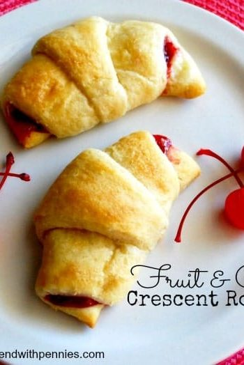 fruit and cream crescent rolls with cherries on the side, on a white plate