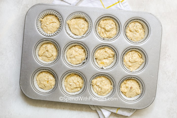 Banana cupcake batter in a lined muffin tray.