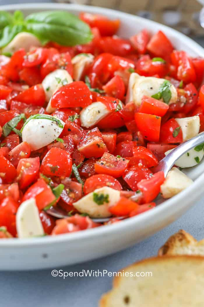 Spooning Caprese Bruschetta out of a white bowl