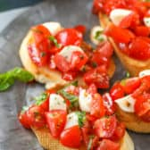 Several pieces of Caprese Bruschetta on a gray plate