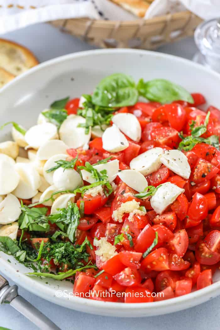 A bowl of caprese bruschetta ingredients ready to be tossed.
