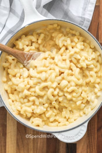 Creamy mac and cheese in a pot with a wooden spoon