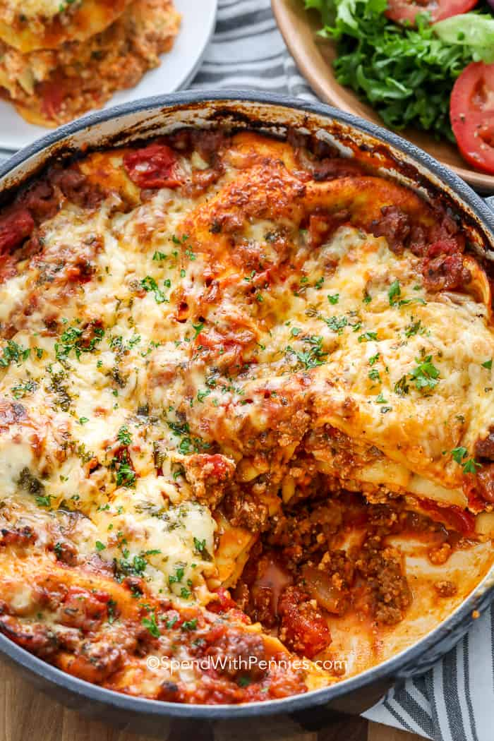 One Pot Lasagna with a slice missing served with salad