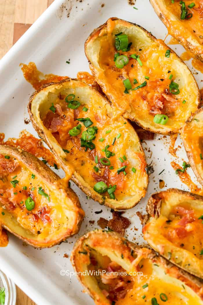 Golden, homemade potato skins lined up on a white baking dish and garnished with chives and green onion