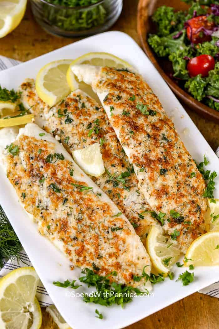 Parmesan Crusted Tilapia on a plate with lemons and parsley.