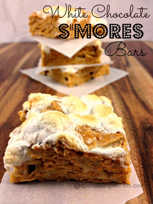 white chocolate s'mores squares with marshmallow topping with a stack in the background