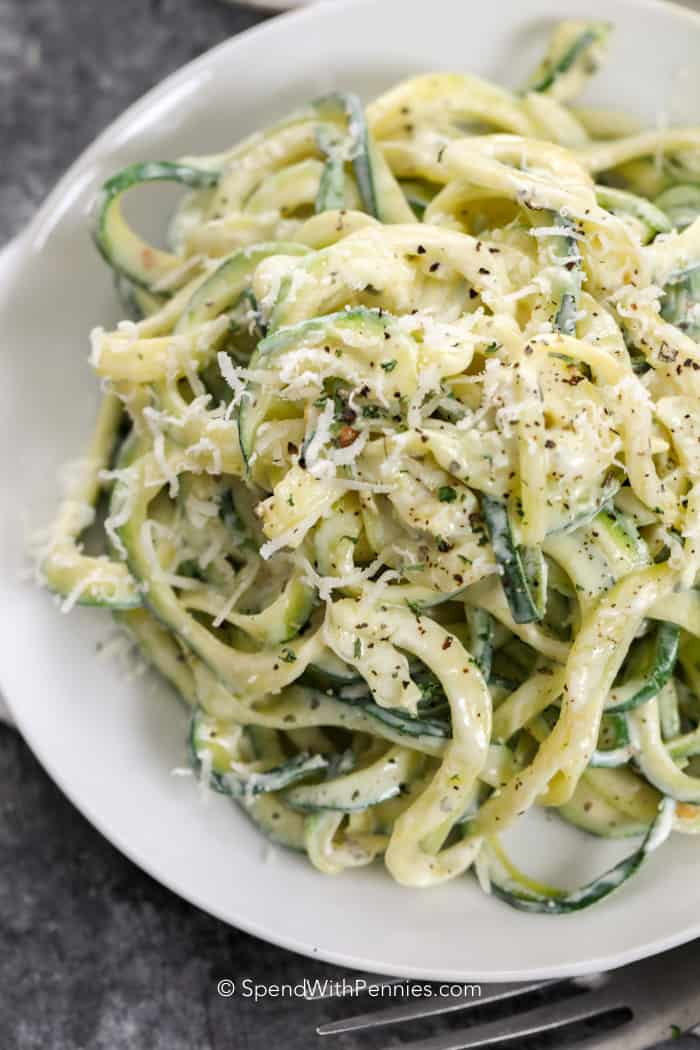 Creamy zoodles on a plate covered in fresh parmesan cheese and pepper.