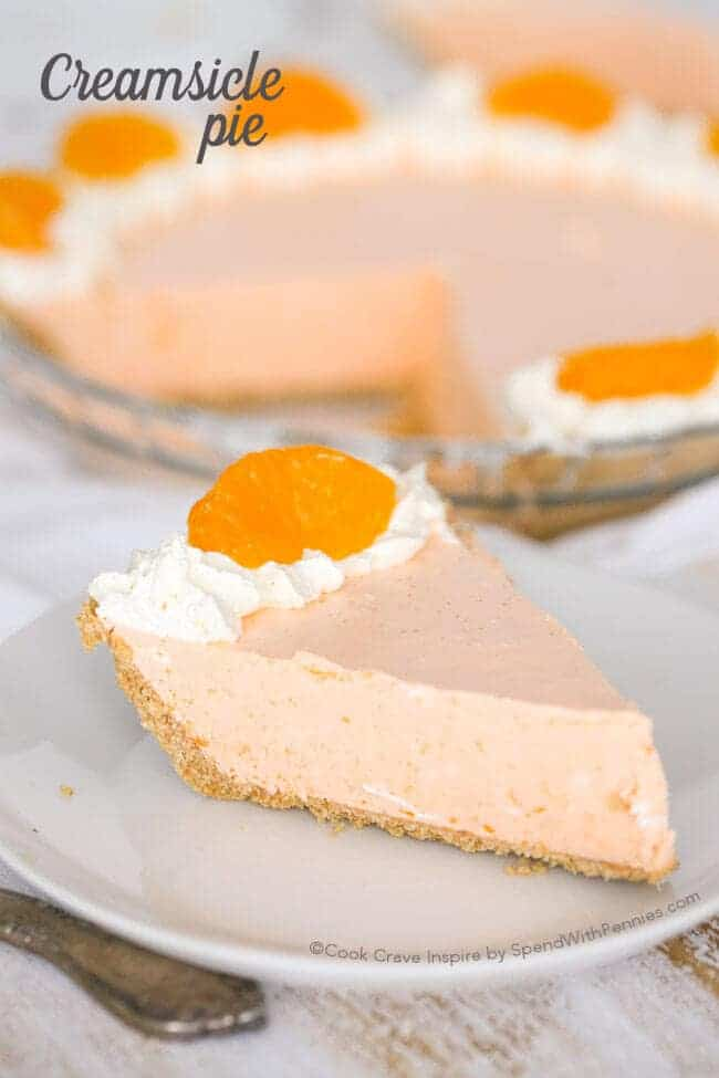 Creamsicle Pie on a white plate with whole pie in the background with slice out of it, with a title