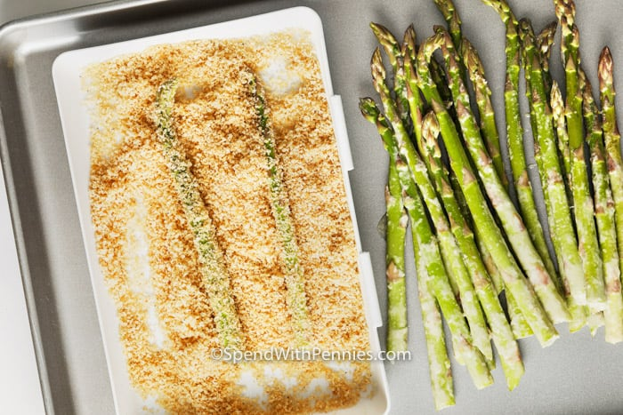 asparagus fries being breaded on a baking sheet