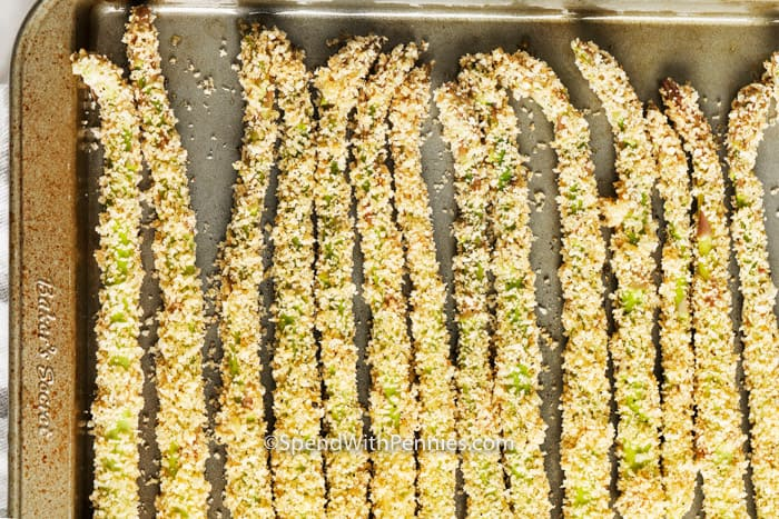 Breaded asparagus fries on baking sheet