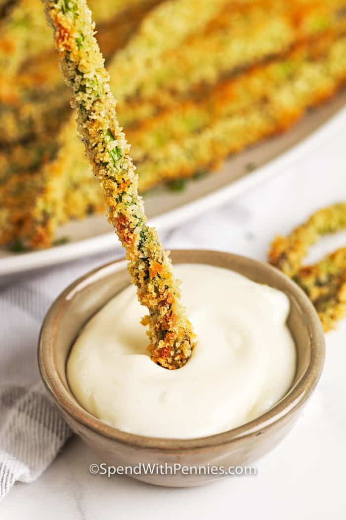 Breaded asparagus fries being dipped into aioli in a bowl