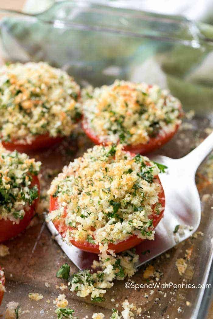 Oven Roasted Tomatoes in a clear baking dish, lifting one out with a spatula