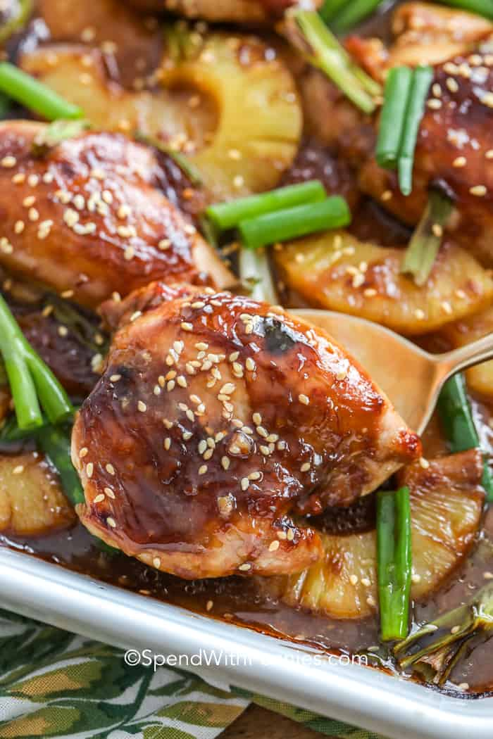 A spoon lifting a baked pineapple teriyaki chicken breast out of a baking dish.