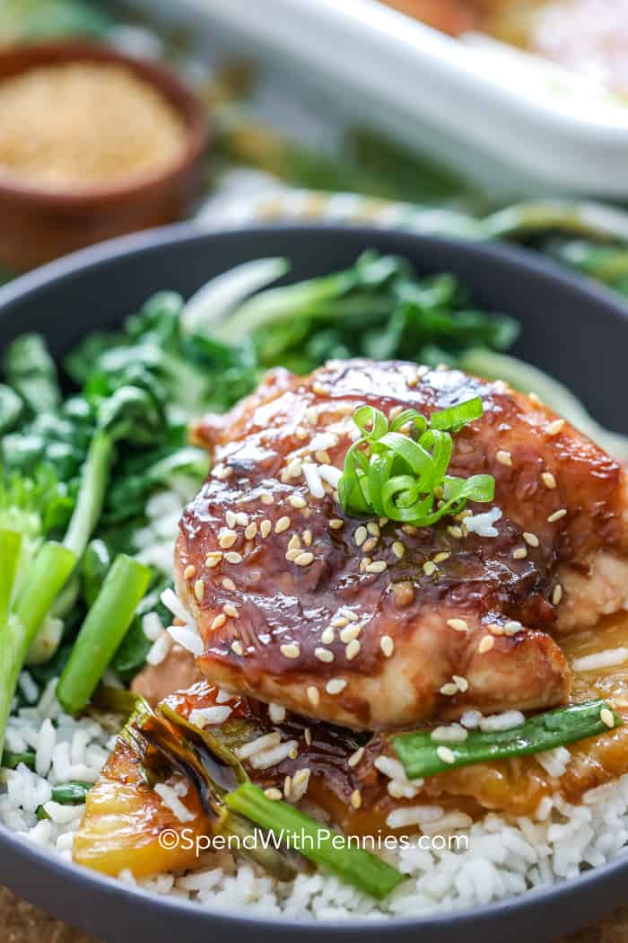A bowl of pineapple teriyaki chicken on a bed of rice with steamed bok choi and fresh green onions.