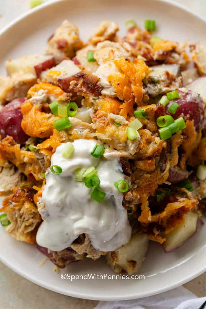 a close up of potatoes, cheese and chicken on a plate topped with sour cream