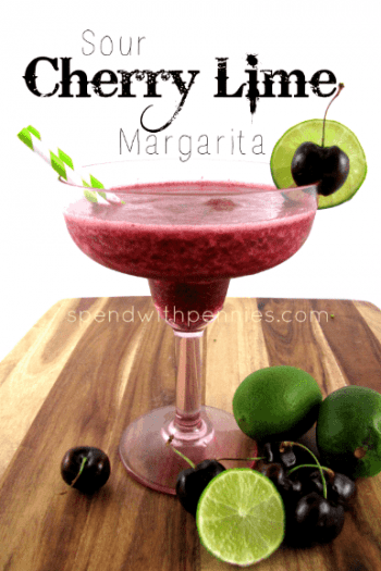 Sour cherry lime margarita in a fancy glass on a wood board with limes and cherries in front