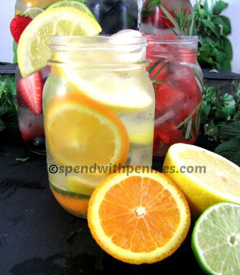 citrus kiss flavored water with Lemons, limes and oranges in front