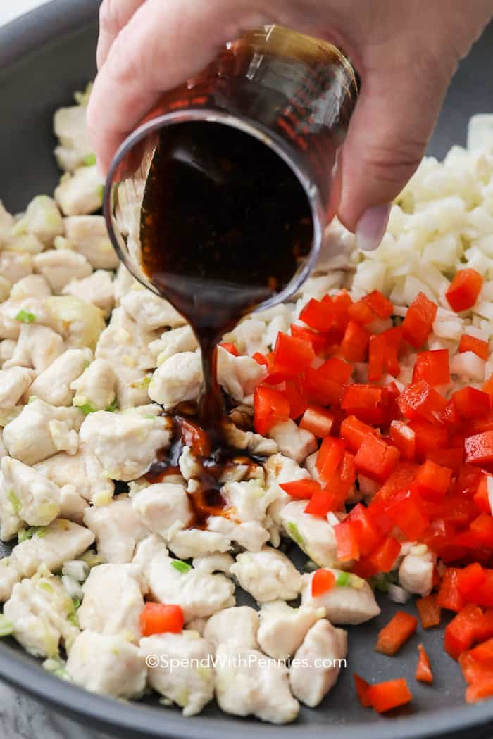 Lettuce wrap sauce being poured over cooked chicken and diced peppers.