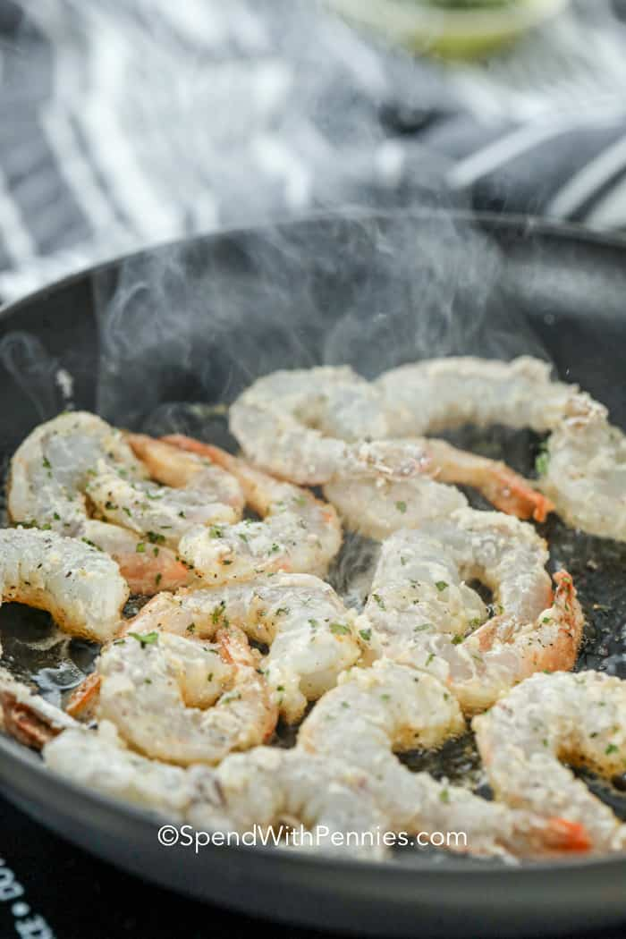 Lemon pepper shrimp being fried in a pan.