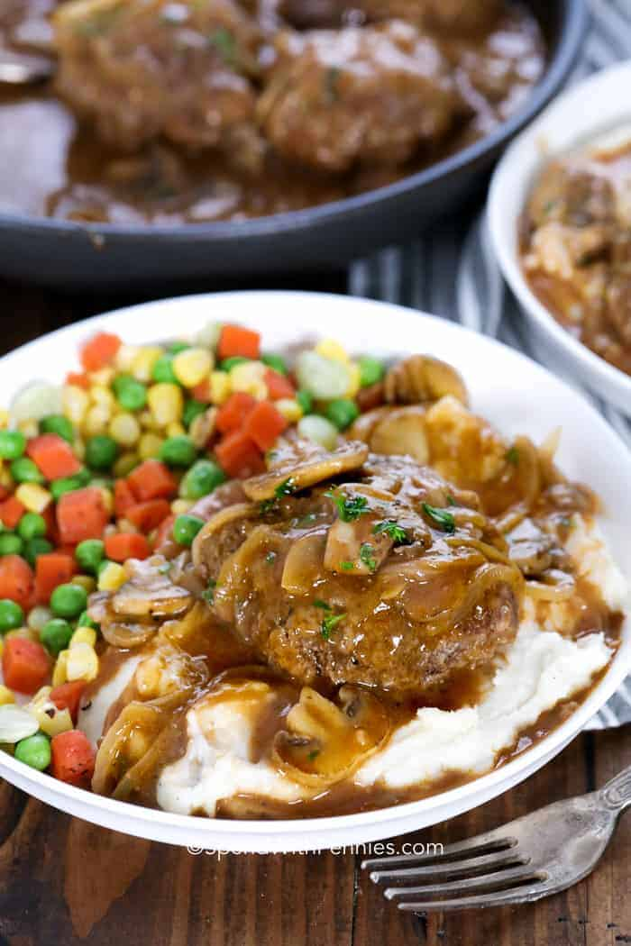 Mushroom Salisbury Steak over mashed potatoes served with mixed vegetables on a plate