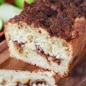 Slice apple pie bread loaf on a cutting board and green apples in the background
