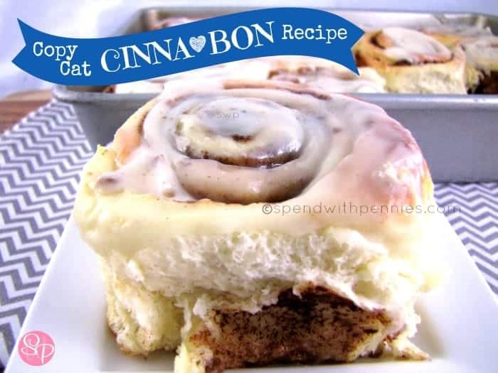 single copy cat cinnabon with frosting on a white plate with a tray of cinnamon buns in the background