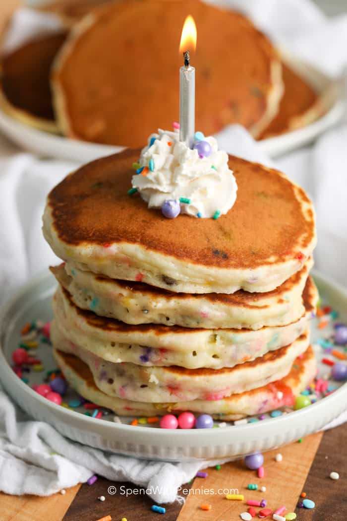 A stack of birthday cake pancakes with a candle on top