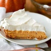 Slice of pumpkin cheesecake on a white plate, with a pumpkin in the background