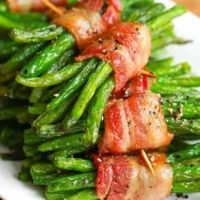 a stack of bacon wrapped green bean bundles on a white plate