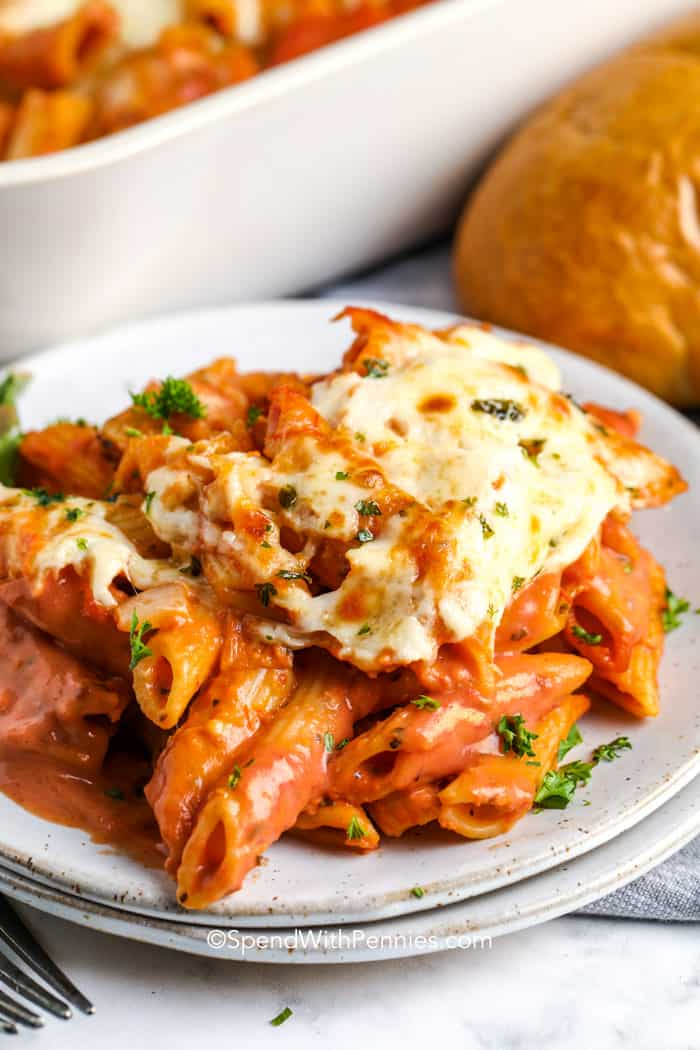 Creamy tomato pasta topped with cheese and parsley on a plate