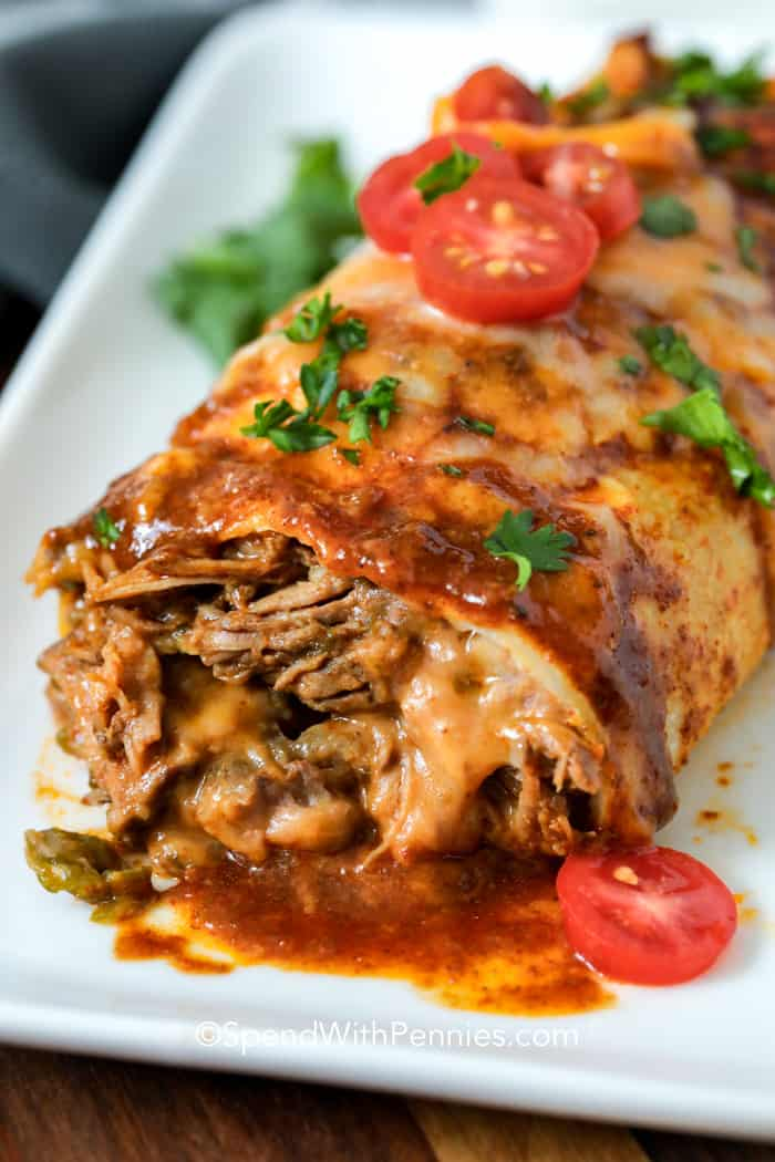 Slow cooker beef burrito on a plate garnish with parsley and tomato