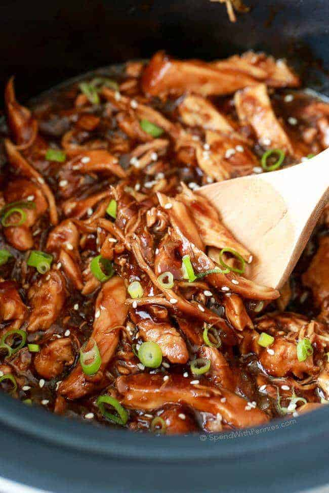 Spoon Stirring crock pot honey garlic chicken in slow cooker