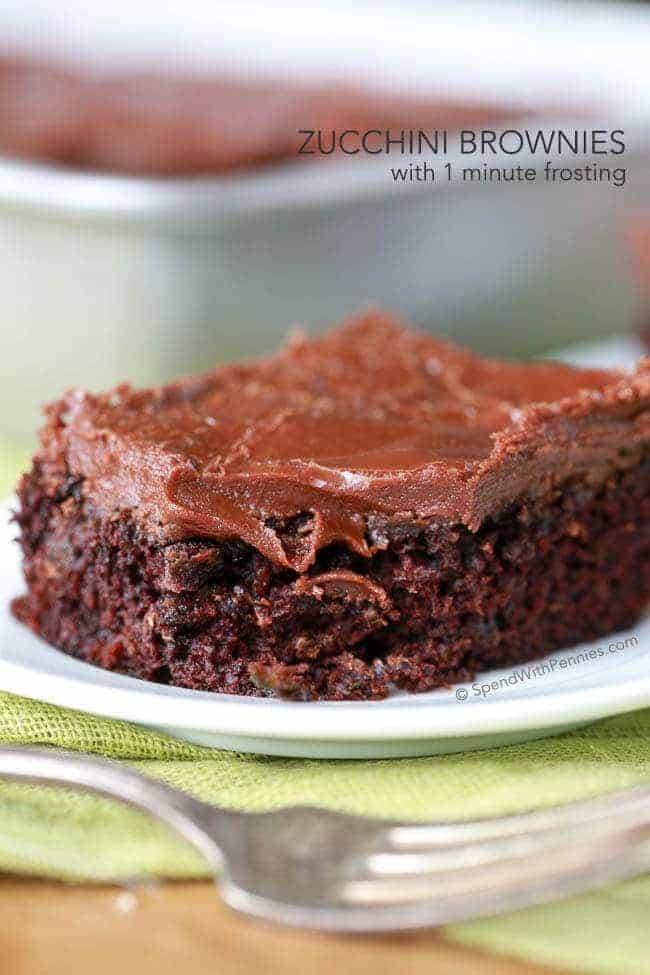 Zucchini Brownie on a white plate with fork in foreground and pan of them in the background with text