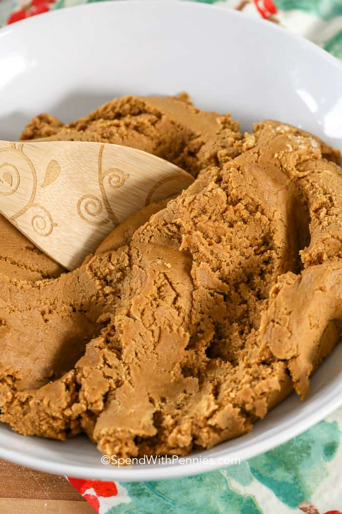Gingerbread cookie dough being mixed in a white bowl with a wooden spoon.