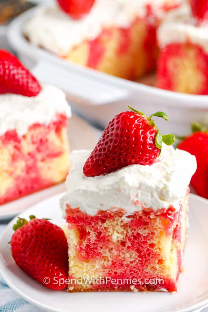 A slice of strawberry poke cake with whipped topping and a strawberry on top