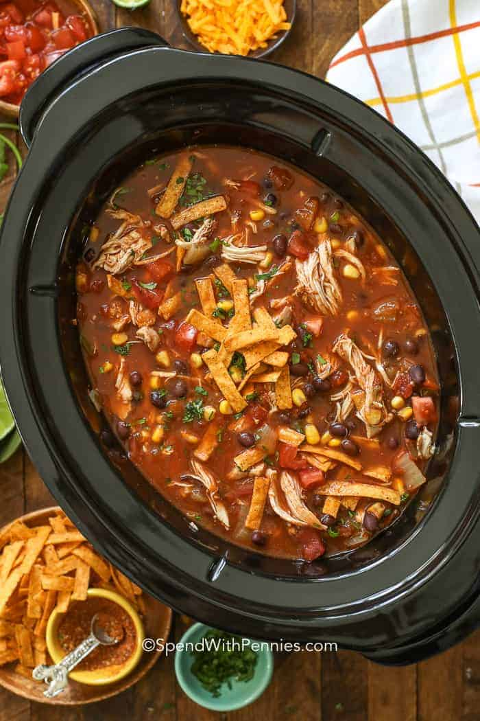 A Crock Pot full of slow cooker tortilla soup with tortilla strips.